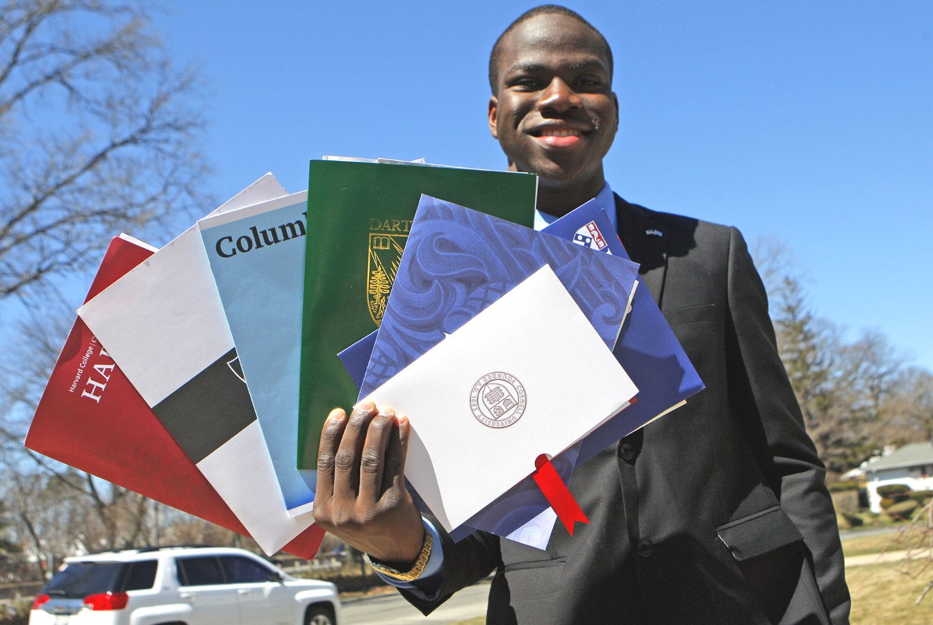 ELMONT, NY - April 4, 2015: This is a picture of Harold Ekeh 17 at his house a 459 Parkway Dr. holding 7 Ivy League College Pamphlets. Mr. Ekeh was accepted to 8 Ivy League colleges. (Photo by Victor Alcorn) PHOTO CREDIT GOES TO VICTORALCORN.COM